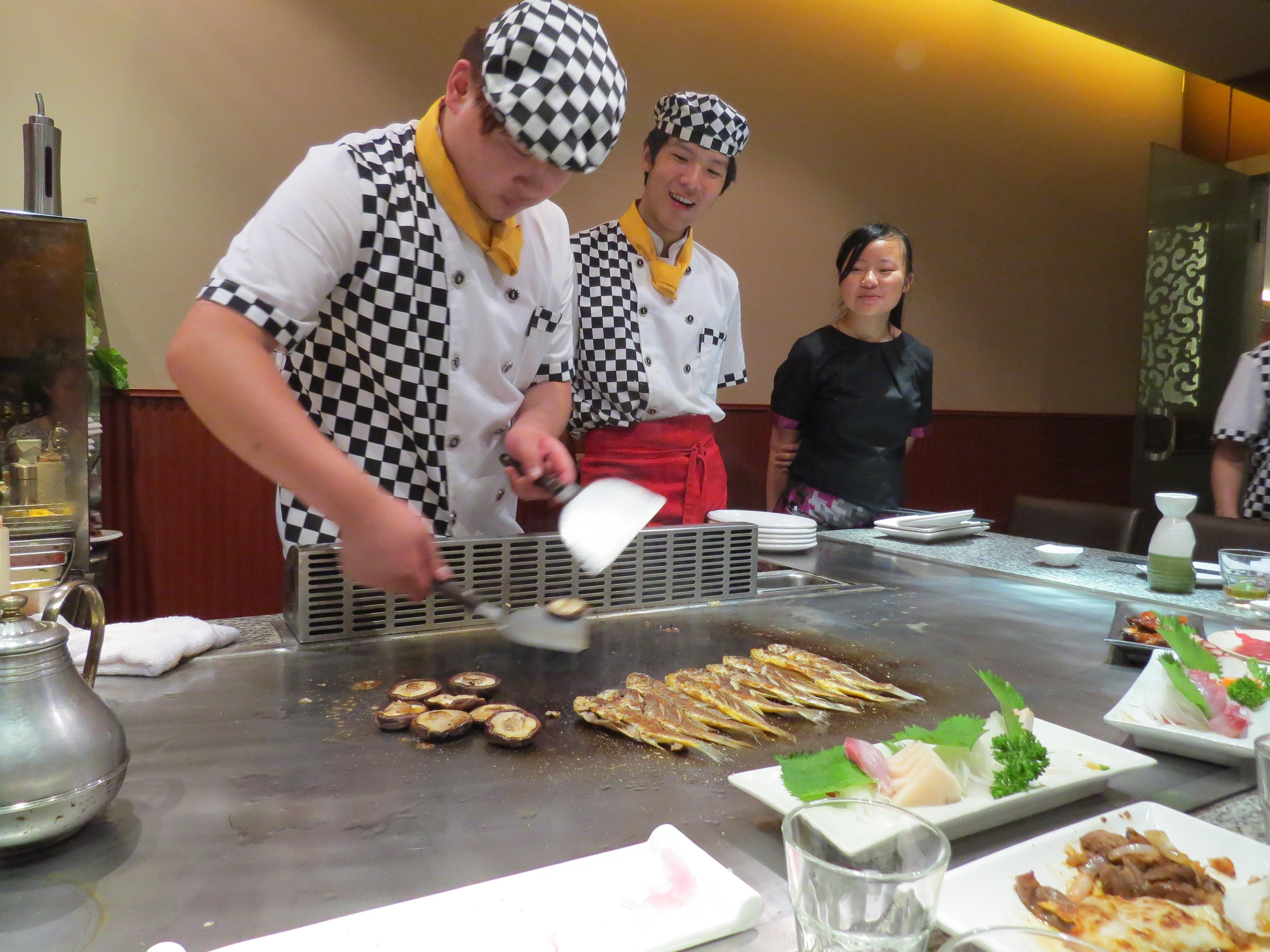 Kucharze gotujący przed gośćmi