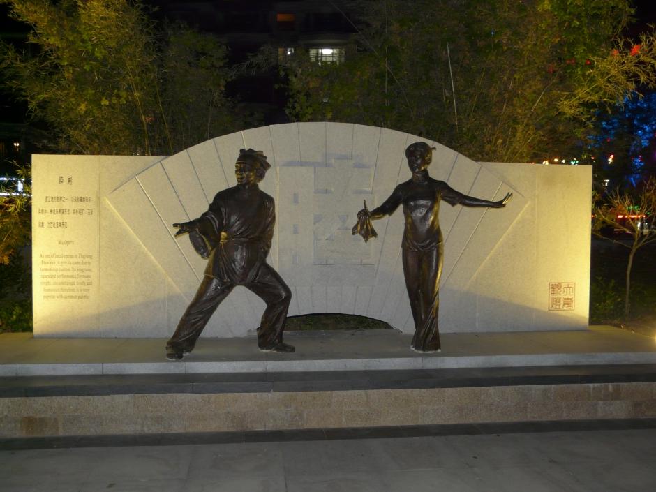 Pomnik w jednym z parków, w którym kobiety tańczą a mężczyźni ćwiczą tai chi